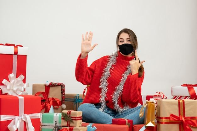 Jeune fille avec pull rouge et masque noir faisant signe de pistolet assis autour de cadeaux sur blanc