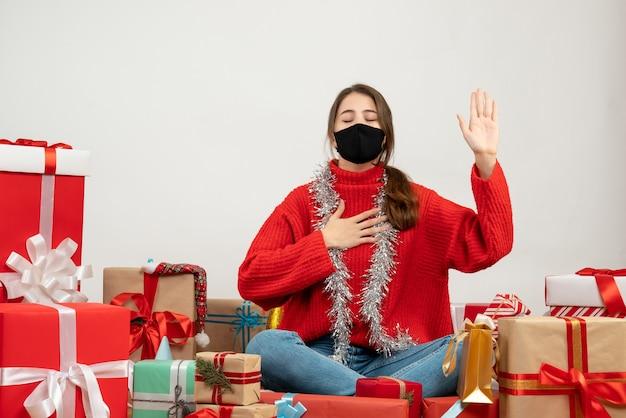 Jeune fille avec pull rouge et masque noir faisant signe de promesse assis autour de cadeaux sur blanc