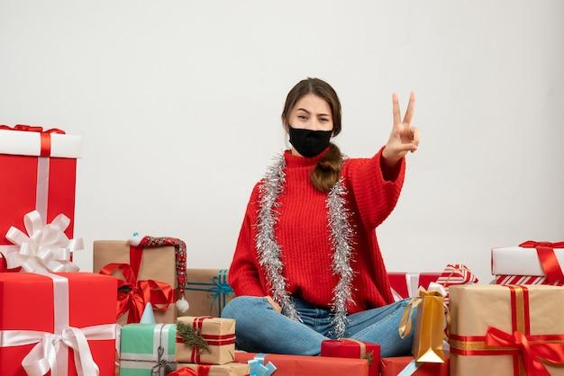 Jeune fille avec pull rouge et masque noir faisant signe de la victoire assis autour de cadeaux sur blanc