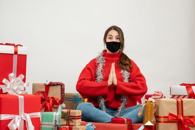 Jeune fille avec pull rouge et masque noir faisant signe de voeux mains assis autour de cadeaux sur blanc