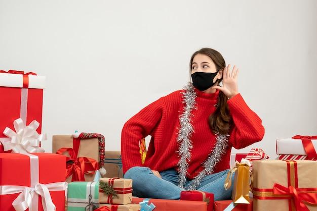 Jeune fille avec pull rouge et masque noir mettant la main à son oreille assis autour de cadeaux de noël sur blanc