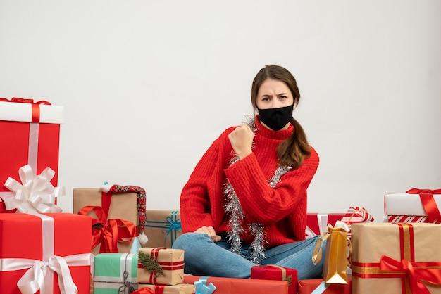 Jeune fille avec pull rouge et masque noir montrant la force assis autour de cadeaux sur blanc
