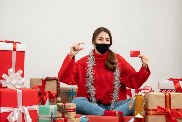 Jeune fille avec pull rouge et masque noir tenant une carte de crédit assis autour de cadeaux sur blanc