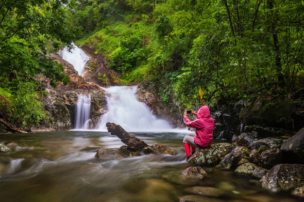La jeune fille en pull rouge en tournée sur la cascade pi-tu-gro, belle cascade dans la province de tak, thaïlande.