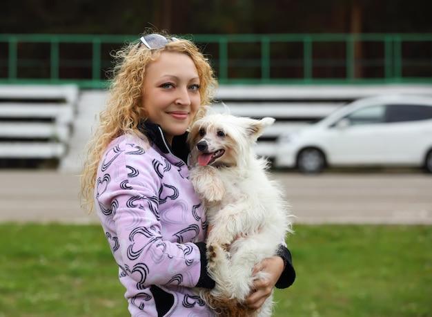 Jeune fille qui marche et la formation de son chien de berger bucovine sur une route vide rurale