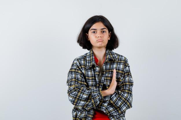 Jeune fille qui s'étend de la main pour s'arrêter en chemise à carreaux et t-shirt rouge et à l'air sérieux, vue de face.