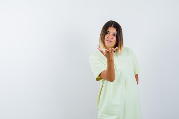 Jeune fille qui tend la main vers la caméra comme tenant quelque chose en t-shirt et à la recherche de sérieux. vue de face.