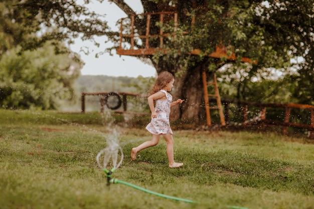 Jeune fille qui traverse les éclaboussures d'eau sur la clairière verte