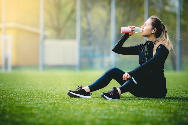 Jeune fille de race blanche attrayante en costume de sport au repos après avoir couru dans le parc, assis sur l'eau potable de l'herbe et souriant en profitant de ses écouteurs sans fil
