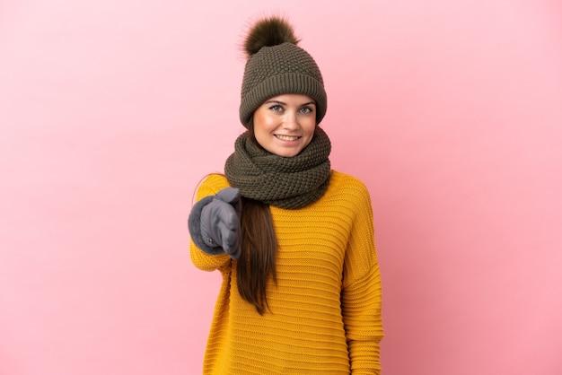 Jeune fille de race blanche avec chapeau d'hiver isolé sur fond rose se serrant la main pour conclure une bonne affaire