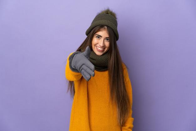 Jeune fille de race blanche avec chapeau d'hiver isolé sur fond violet se serrant la main pour conclure une bonne affaire