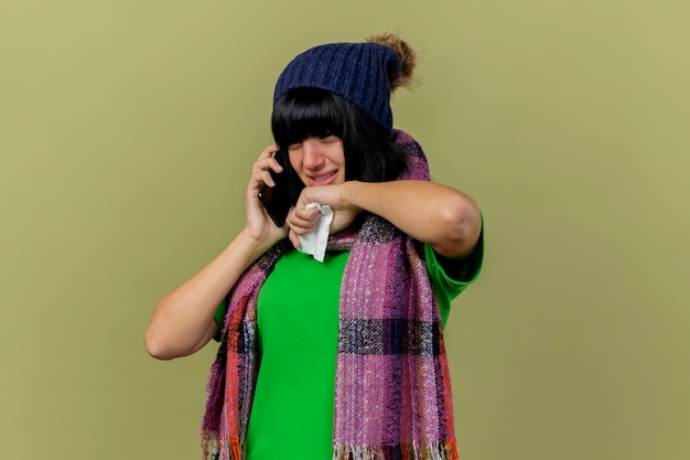 Jeune fille de race blanche malade portant un chapeau d'hiver et une écharpe parler au téléphone à la main tenant une serviette en touchant le menton isolé sur fond vert olive avec espace de copie
