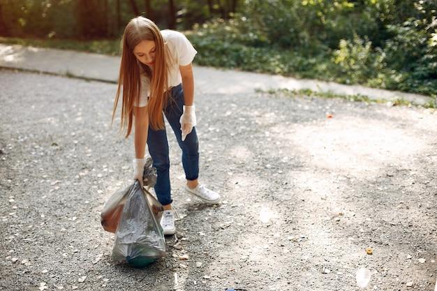Jeune fille ramasse des ordures dans des sacs à ordures dans le parc