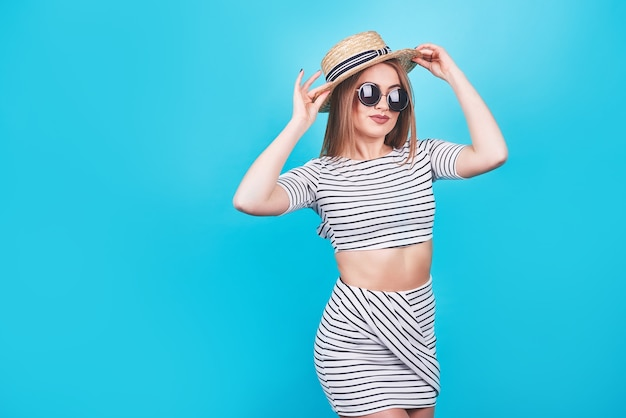 Jeune fille à rayures blanches et noires, chapeau, lunettes de soleil, bouche ouverte émotionnellement sur un fond bleu vif avec un corps parfait. isolé. prise de vue en studio.