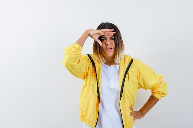Jeune fille à la recherche de loin avec la main sur la tête, mettant la main sur la taille en t-shirt blanc, veste jaune et à la recherche concentrée. vue de face.