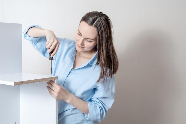 Jeune fille recueille des meubles avec un tournevis, espace copie.