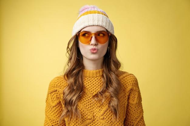 Jeune fille réfléchie glamour élégante faire des lèvres pliantes desicion pensant idiot en choisissant le produit détourner le regard vers la gauche portant des lunettes de soleil chapeau pull chaud profitant de la station de ski de vacances, fond jaune