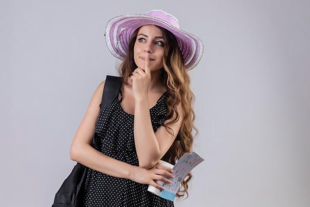 Jeune fille réfléchie de voyageur en chapeau d'été avec sac à dos tenant des billets d'avion à côté de la pensée positive debout sur fond blanc