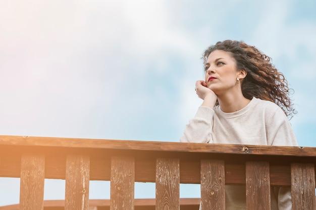 Jeune fille regardant ailleurs avec le ciel en arrière-plan. concept de pensées. image avec espace de copie