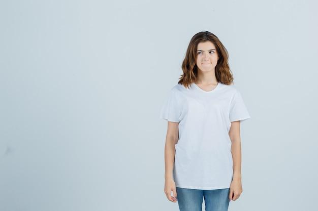 Jeune fille regardant de côté, serrant les lèvres en t-shirt blanc et regardant pensif, vue de face.