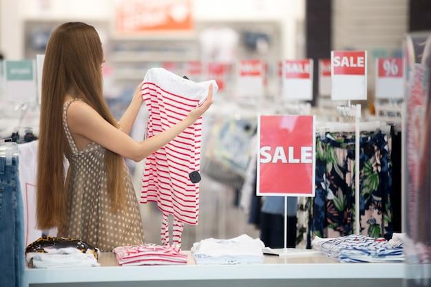 Jeune fille regardant une jupe rouge et rayures blanches