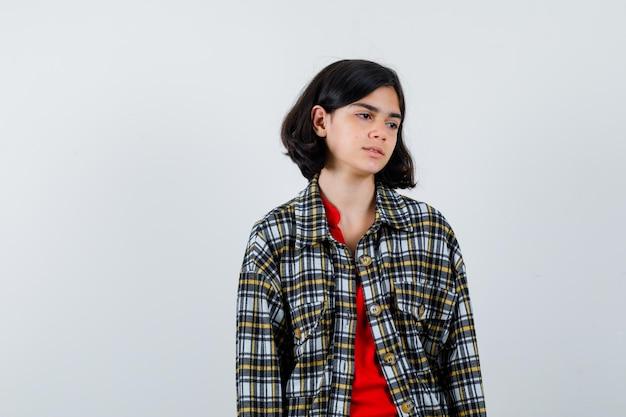 Jeune fille regardant loin tout en se présentant à la caméra en chemise à carreaux et t-shirt rouge et l'air sérieux, vue de face.