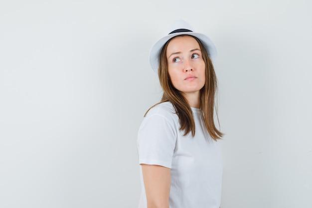 Jeune fille regardant en t-shirt blanc, chapeau et à la recherche concentrée. vue de face.