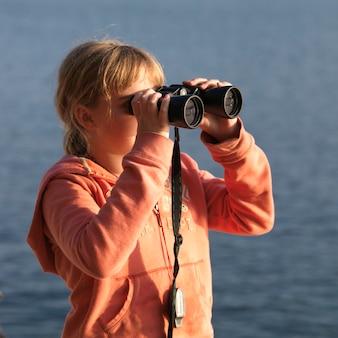 Jeune fille regardant à travers des jumelles au lac des bois, en ontario