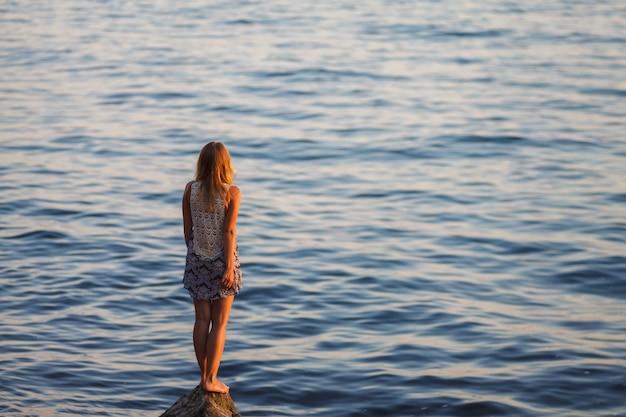 La jeune fille regarde le coucher de soleil sur la mer