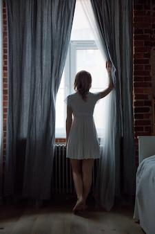 Une jeune fille regarde derrière les rideaux