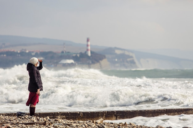 La jeune fille regarde la mer face aux vagues de tempête, aux vagues d'écume, au phare et aux rochers. la fille est vêtue d'une veste noire, d'un bonnet en tricot blanc, d'une jupe longue bordeaux et de bottes noires.
