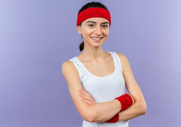 Jeune fille de remise en forme sportswear avec bandeau avec sourire confiant debout sur un mur violet