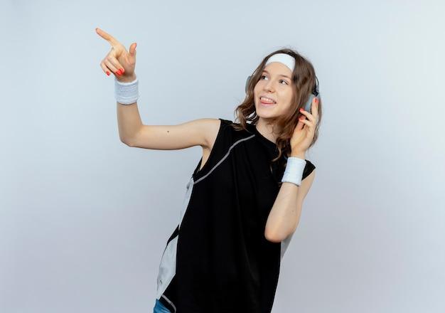 Jeune fille de remise en forme en sportswear noir avec bandeau et casque à côté souriant pointant avec le doigt sur quelque chose debout sur un mur blanc