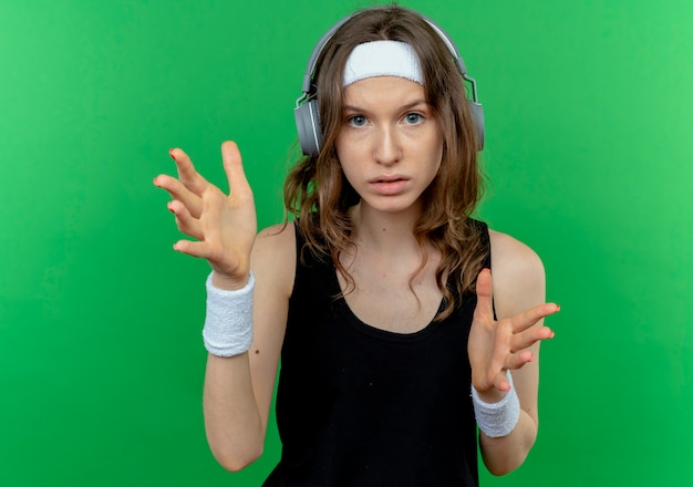 Jeune fille de remise en forme en sportswear noir avec bandeau avec casque avec visage sérieux faisant des gestes avec les mains debout sur le mur vert