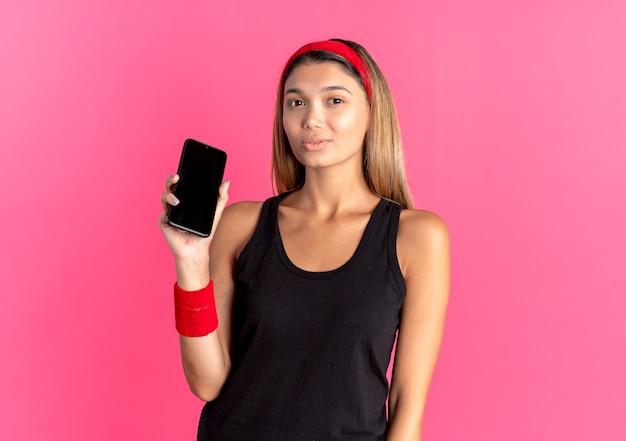 Jeune fille de remise en forme en sportswear noir et bandeau rouge montrant smartphone à la confiance debout sur le mur rose