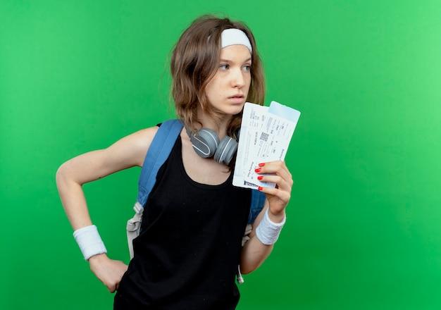 Jeune fille de remise en forme en sportswear noir avec bandeau et sac à dos tenant des billets d'avion à côté avec un visage sérieux debout sur un mur vert