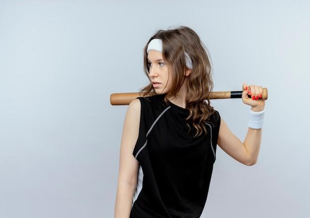 Jeune fille de remise en forme en sportswear noir avec bandeau tenant la chauve-souris basaball à côté avec visage sérieux debout sur un mur blanc