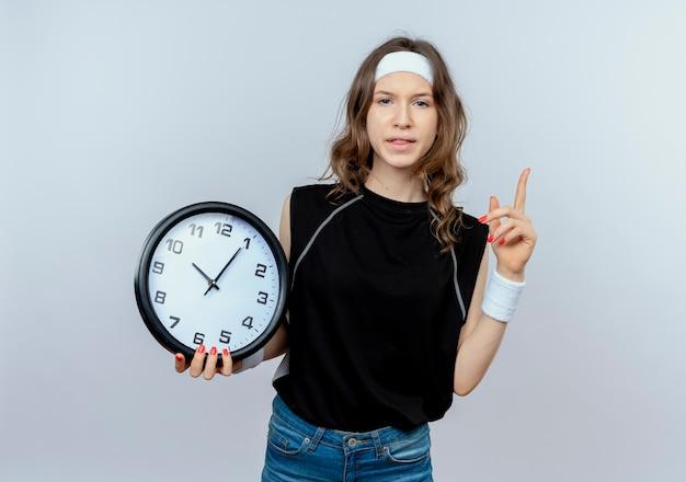 Jeune fille de remise en forme en sportswear noir avec bandeau tenant horloge murale montrant l'index d'avertissement debout sur un mur blanc