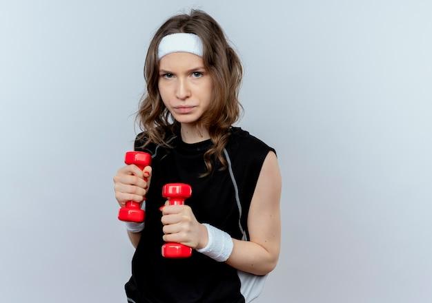 Jeune fille de remise en forme en sportswear noir avec bandeau travaillant avec des haltères avec un visage sérieux debout sur un mur blanc