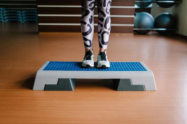 Jeune fille de remise en forme en vêtements de sport et chaussures, jambes debout sur la plate-forme step.