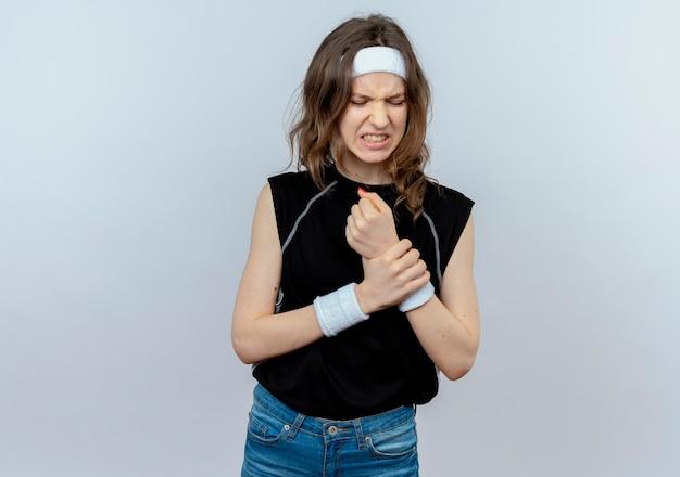 Jeune fille de remise en forme en vêtements de sport noir avec bandeau touchant son poignet à la souffrance souffrant de douleur debout sur un mur blanc