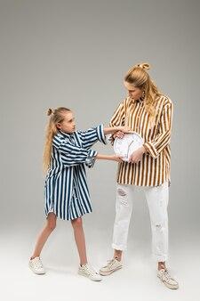 Jeune fille résolue tenant fermement une horloge ronde avec les deux mains pendant que son ami aîné l'enlève