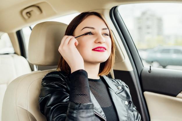 Jeune fille retouche son maquillage tout en étant arrêté dans la circulation