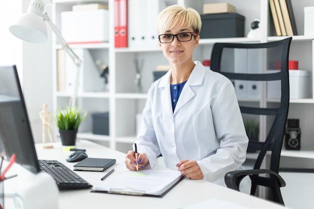 Une jeune fille en robe blanche assise à la table et tenant un stylo.