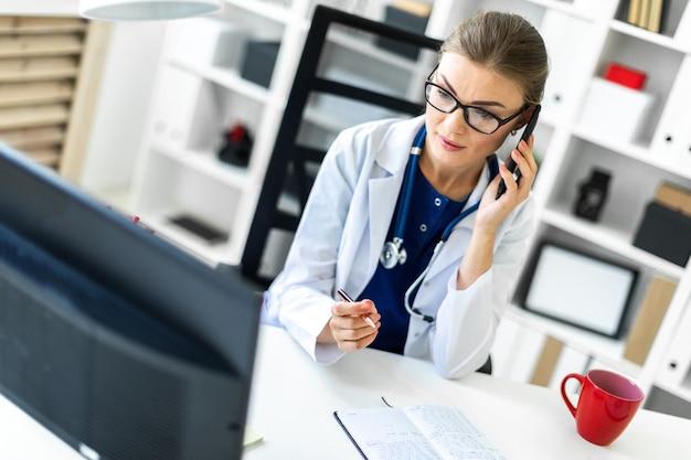 Une jeune fille en robe blanche est assise au bureau du bureau, parlant au téléphone et tenant un stylo à la main. un stéthoscope pend autour de son cou.