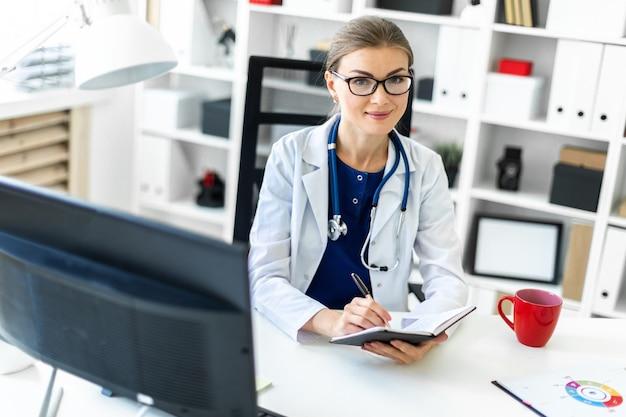 Une jeune fille en robe blanche est assise à une table dans le bureau et tient un stylo et un cahier à la main