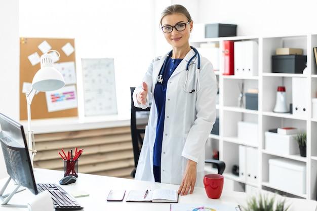 Une jeune fille en robe blanche se tient près du bureau du bureau et étend sa main droite en avant.