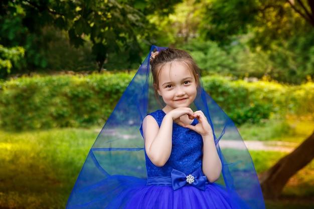 Jeune fille en robe bleue anniversaire dans le parc. sourire enfant en plein air
