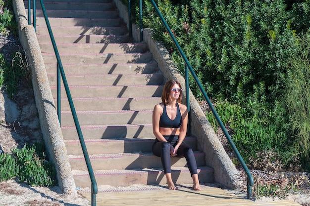Jeune fille en robe de fitness assis sur les marches d'escalier