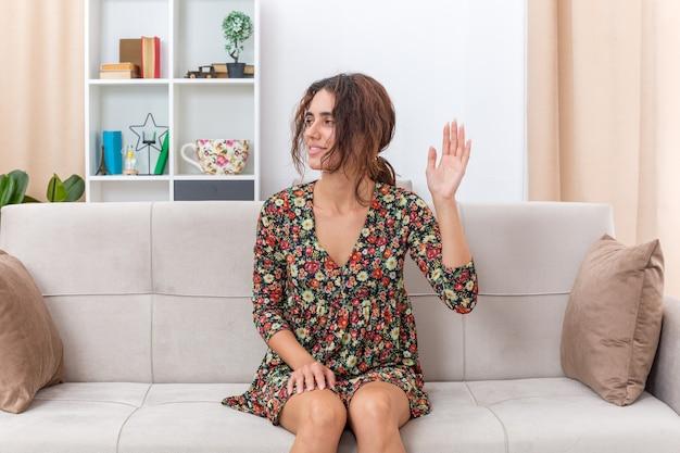 Jeune fille en robe à fleurs regardant de côté un sourire heureux et positif agitant la main assise sur un canapé dans un salon lumineux